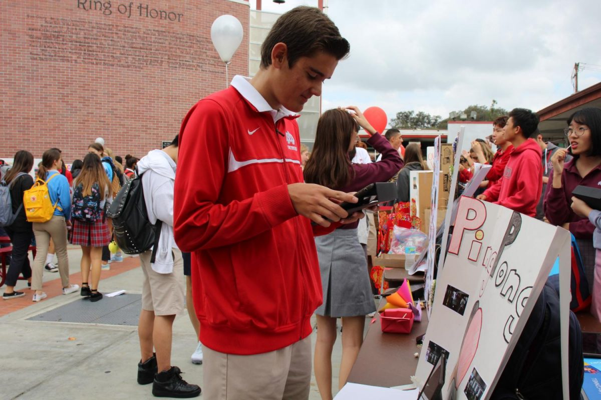 Junior Grant Thomas signs up for Ping Pong Club at Club Fair. Thomas was one of the many students who took an interest in joining.