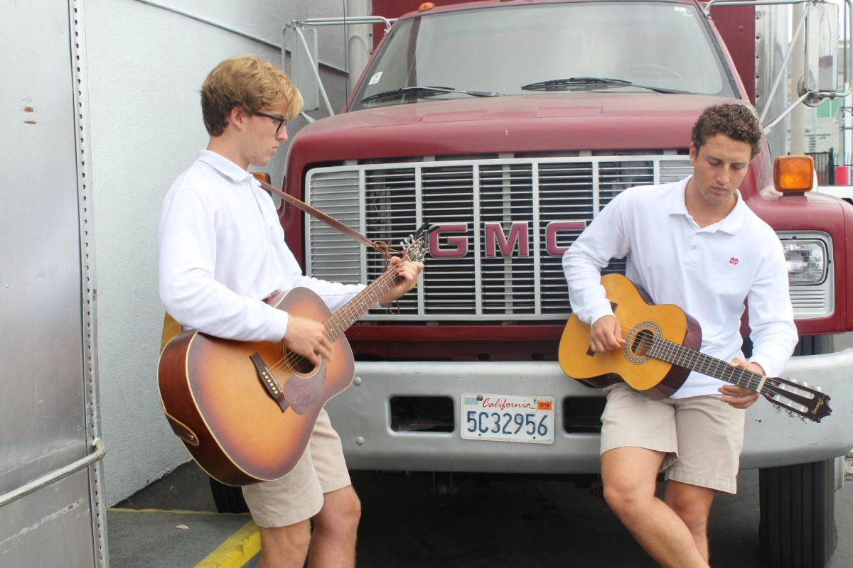 Seniors Jake Armstrong and Vincent Pozzuoli play guitar outside of the band room during the block 4 elective, Guitar Media Production.