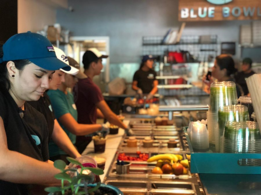 SCOOP THERE IT IS: A Blue Bowl employee scooping pitaya base to prepare a customer's personalized bowl.