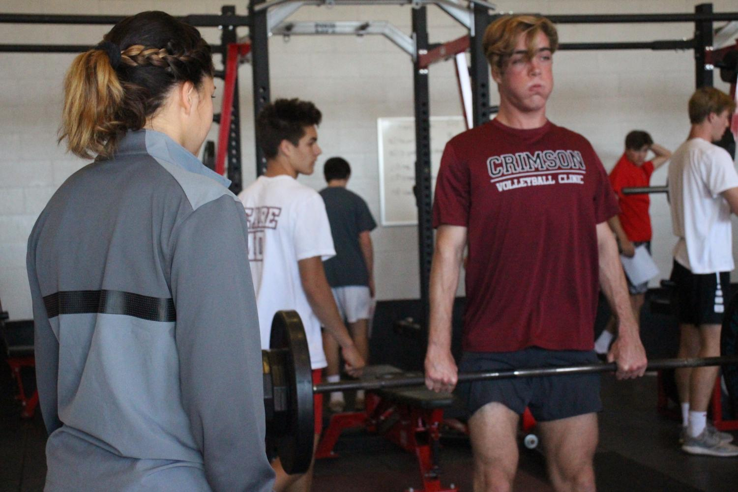 HEAVY+LIFTING%3A+Assistant+strength+and+conditioning+coach+Katie+Guizar+helps+senior+boys+volleyball+player+David+Linkletter+as+he+hang+cleans.+Guizar+has+been+a+coach+at+the+school+for+five+years.+%22I%E2%80%99ve+been+an+athlete+my+whole+life+and+I+remember+the+summer+before+I+went+to+college+I+trained+in+a+facility+and+the+strength+coach...and+I+just+remember+chatting+with+him+and+just+being+intrigued+by+everything+that+he+did+to+make+me+better+and+that+was+just+the+initial+start+of+me+wanting+to+get+into+the+same+industry%2C%22+Guizar+said.%0A