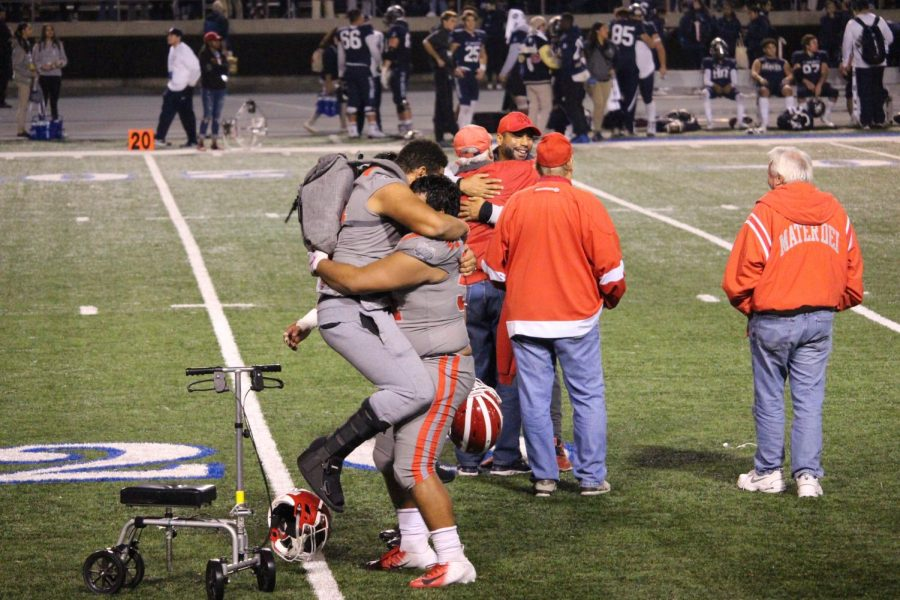 """RING SEASON: Junior offensive lineman Myles Murao and junior defensive lineman Martin Salazar hug it out after finally defeating the Bosco Braves. Murao was injured in a game earlier this season and won't be able to play until his senior year. """"We really hurt when we lost the time before and for it to come full circle and for us to finally beat Bosco is a great feeling,"""" Young said."""