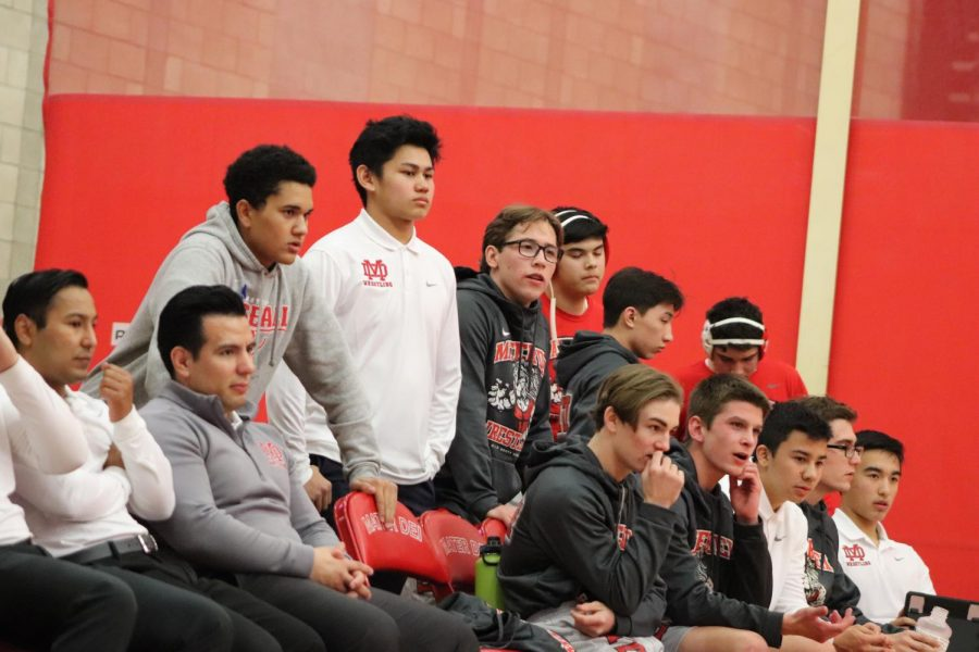 WRESTLING TEAM JOLINS TOGETHER TO SUPPORT SENIORS: The wrestling team anxiously watches their teammates complete against Estancia High School  on Jan. 23. The team cheers on their senior classmates to celebrate the programs senior night.