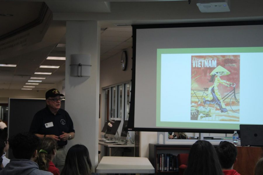 Grimm shows the student a a Vietnam booklet that was given to all the soldiers. This booklet helped soldiers understand the culture and location in where they were stationed.