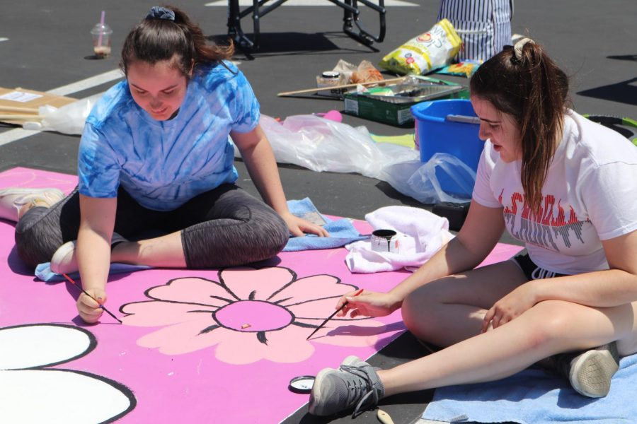 PAINTING PARTY: Senior Beth Romeyn and senior Chloe Savard work together to paint Romeyn's personal parking spot for the 2019-2020 school year on Aug. 12. Romeyn was inspired by the Beatles song,
