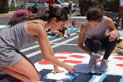 "A FAMILY AFFAIR: Senior Lily Mohtashami paints her spot with her sister during the painting party on Aug. 12. Mohtashami wanted a way to put her name on her parking spot and felt that the best way to display that was with cherries. ""...they're gonna be cherries when I put the stems but I just liked the design and I liked how I could put the cherries in 2020,"" Mohtashami said."