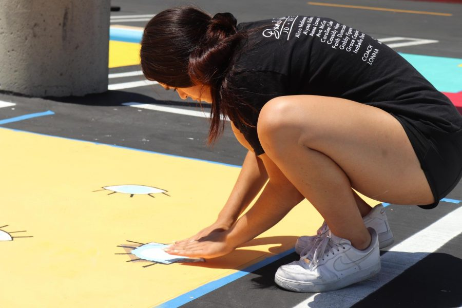 PAINTING THE PICTURE: Senior Cassidy Meyer starts to paint the design on her personal parking spot on Aug. 12.