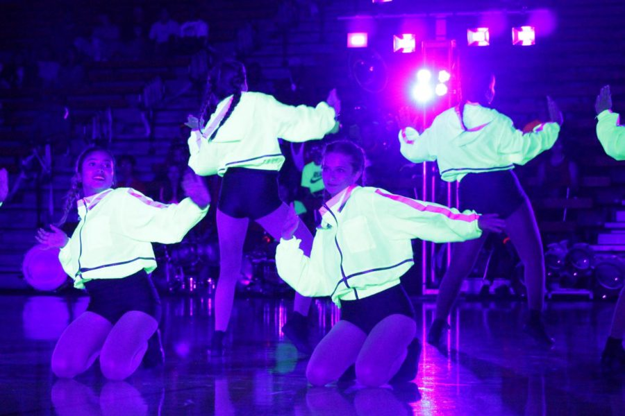 "GLOW IN THE DANCE:  In their team debut, All Female performed at The Homecoming Showcase Night Rally on Oct. 10. ""I don't care if you can dance [or] if you have taken a class one time, anybody can dance,"" senior Faith McGrath said. ""If you can get up and more your body if you can move anything at all you can dance."""