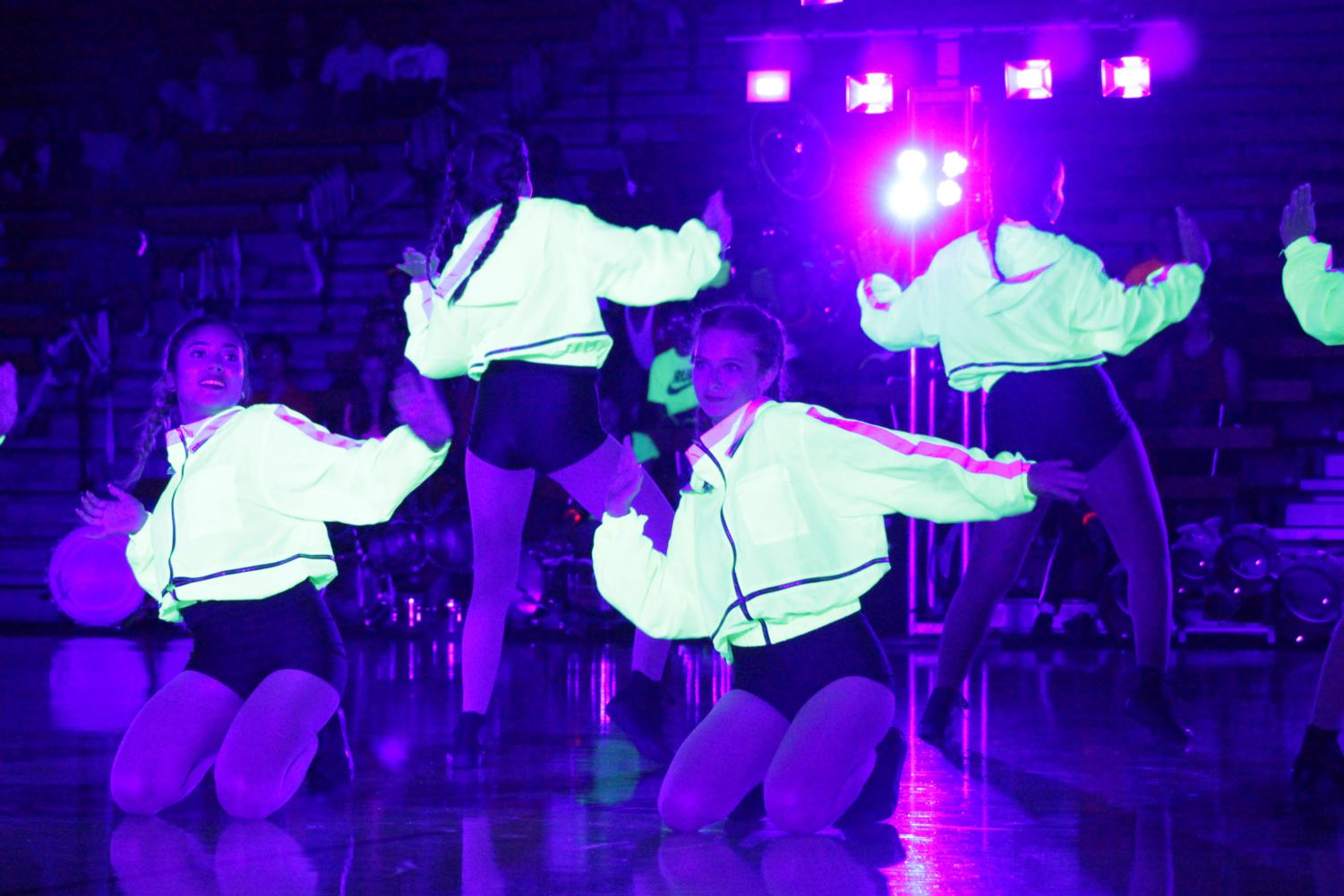 """GLOW IN THE DANCE:  In their team debut, All Female performed at The Homecoming Showcase Night Rally on Oct. 10. """"I don't care if you can dance [or] if you have taken a class one time, anybody can dance,"""" senior Faith McGrath said. """"If you can get up and more your body if you can move anything at all you can dance."""""""