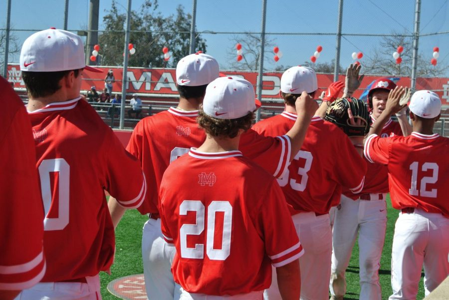 CELEBRATIONS: Senior Brett Nelson is congratulated by his teammates after sliding safely into home plate and scoring a run in the Varsity Red vs. White scrimmage game. The Red and White Day is an annual tradition kicking off baseball season, where all baseball teams play friendly games. The event also included live music, catering, and shopping.