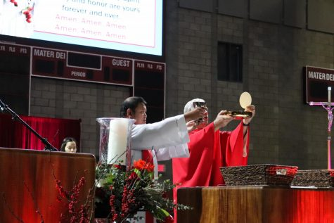 """Cruz and Father Steve Sallot, the new President of Mater Dei, prepare the Body and Blood of Christ for the Eucharist. Cruz works closely with Helen Steves who has worked at Mater Dei for 32 years. """"And I believe his prayerful, intentional preparation is, to me so inspiring. When you walk into a mass...you go in there and you have [for] example 100 football players, and how he takes the Word of God to relate it to their lives. When you walk into a performing arts group, and he, who is a singer himself, he"""