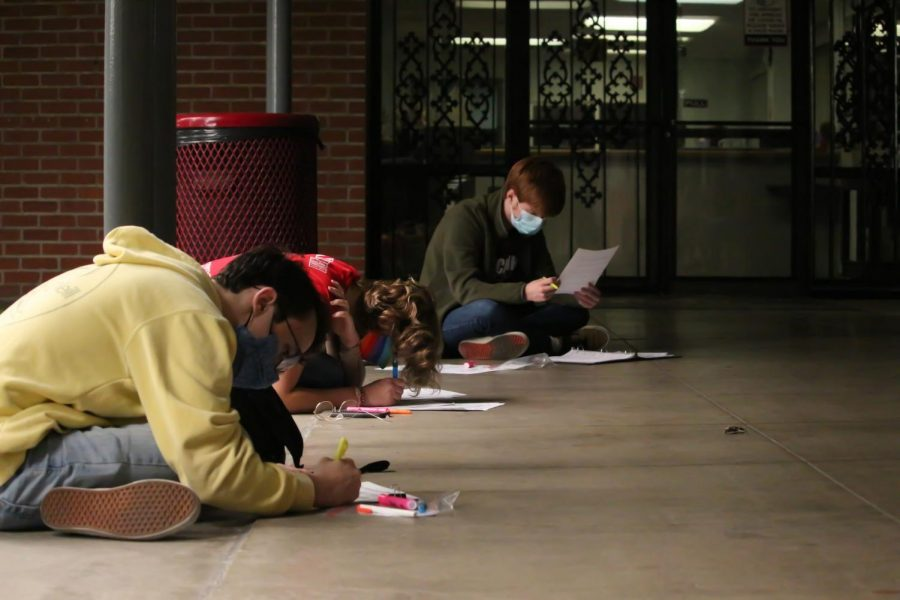 """WITH A LITTLE HELP FROM MY FRIENDS: Sitting in the walkway by the grotto, seniors William Gibson and Christopher Mott and junior Margaret Hohenstein concentrate on annotating their music. """"Handbells is a really great group and it's been amazing to get together with them in person and ring,"""" Hohenstein said."""