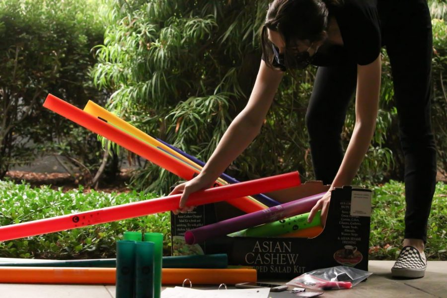 "MIX AND MATCH: Hunched over, senior Natalie Erhard organizes the Boomwhackers into piles. Erhard separates them in order to easily identify which instrument plays what note. ""Music to me is a way for people to come together and express their art. It's really just a place for artists to come together, tell stories, and just entertain others and give them an escape from whatever is going on in life,"" Erhard said."