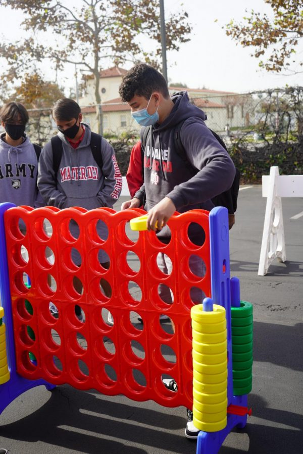 "BUILDING COMMUNITY: Freshmen Antonio Taormina, Mikey Erickson, and Santiago Lopez gather in the Bristol Lot for a game of Connect Four. Connect Four was just one of the many games offered during Freshman Fun Day. Other options included cards and checkers. ""I was talking with my friends for a bit and messing around with the games. Overall I thought it was pretty fun,"" Lopez said."