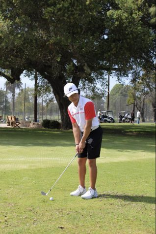 """ABOUT TO SWING: Senior Ryder Henares lines up with the hole to try to sink it in the first swing. Henares and the varsity golf team started the Trinity League this month, which included this match against JSerra. """"We had a feeling we were going to have a season because golf is already a socially distant sport,"""" Henares said. """"However, everyone was excited when the news got out."""""""