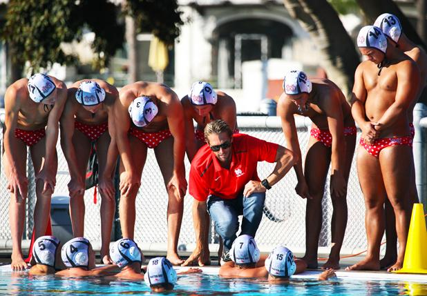 Coach Segesman meets with boys varsity water polo at a timeout to discuss their next plan for attack.