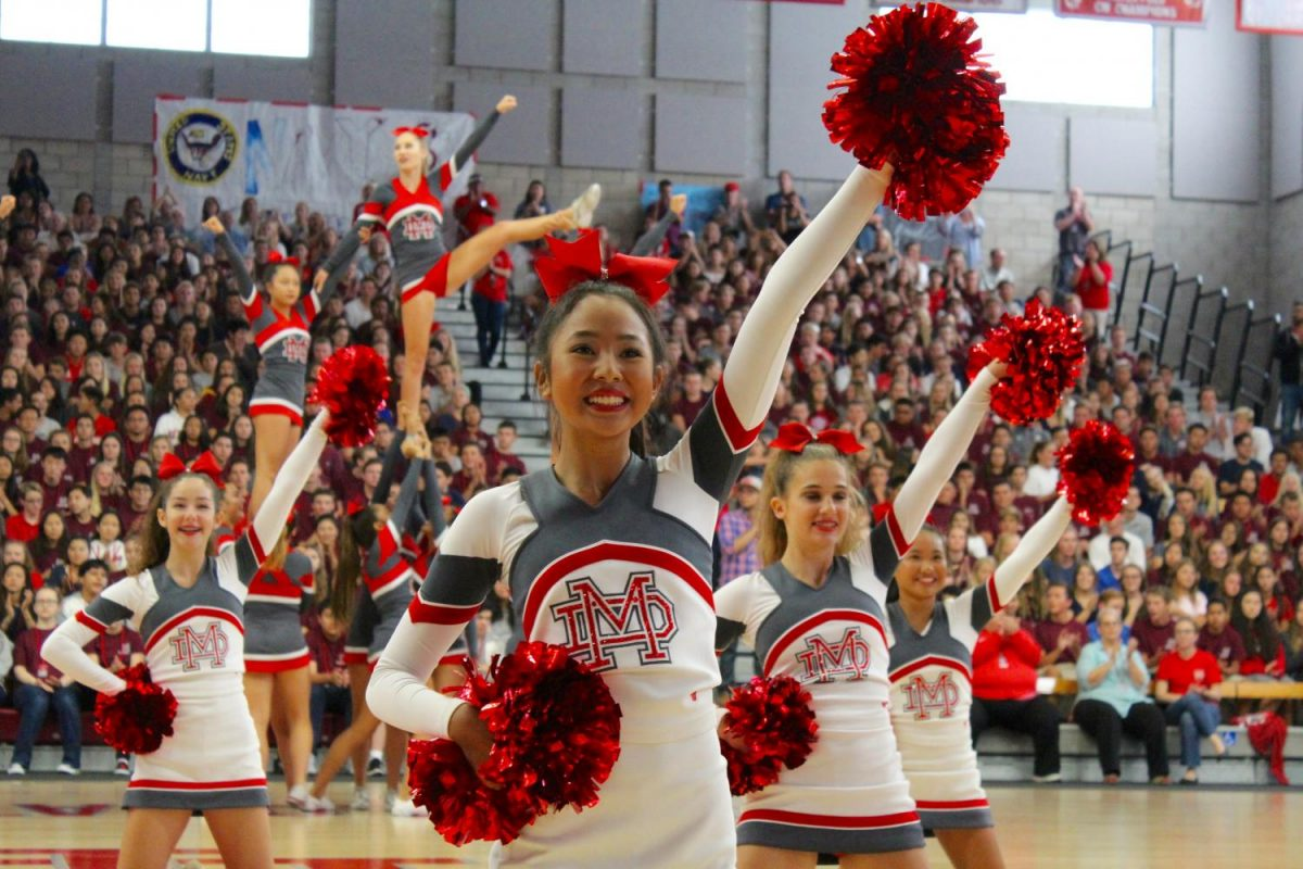 The cheer and song teams perform a dual performance.
