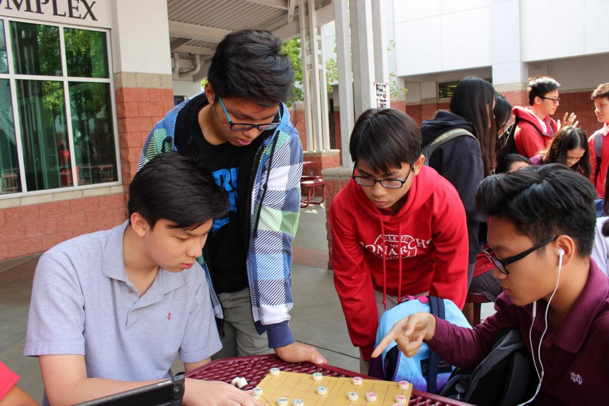 After school (from left to right) Tommy Lam, alumnus Khoi Van, Khoa Thai and Huy Vu play Chinese chess.