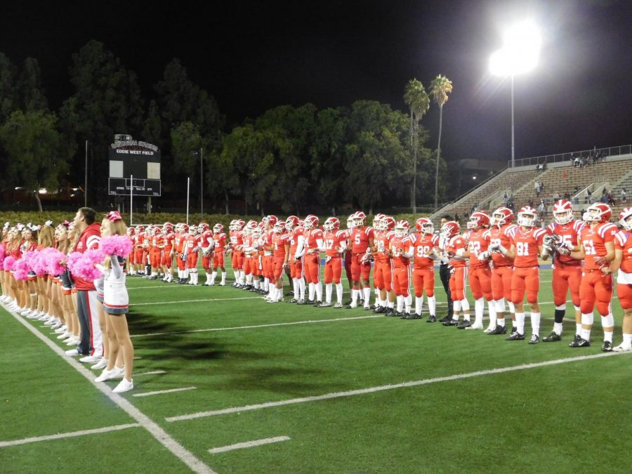 VICTORY: Football players and cheerleaders line up to sing the alma mater at the end of the Homecoming game.
