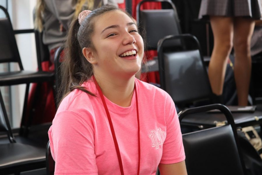 HAVING FUN: Freshman Ashley Morrales wears her pink shirt in choir while sharing a laugh wit other students. Supporting the cause is extremley important to her.