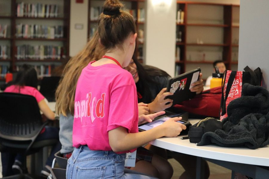 PRETTY IN PINK: Sophomore Sophia Landreville and freshmen Neave Anderson and Faith Nguyen work in the library. Landreville wears the pink shirt in honor of those affected by breast cancer.