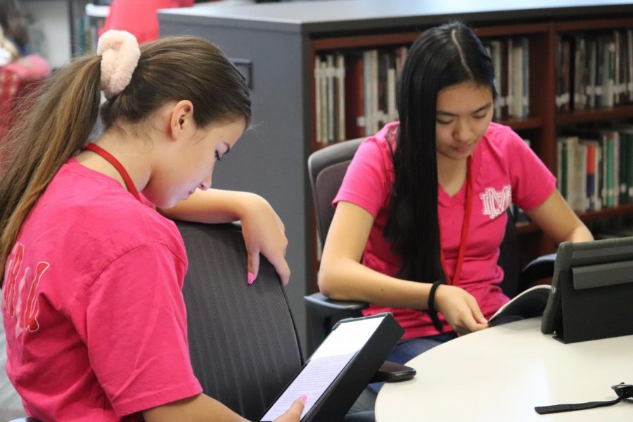 SUPPORTING THE CAUSE: Freshmen Sophia Tebbs and Anne Vu are clad in pin as they work hard in the library. Vu supports the cause in honor of a family member who's been affected.