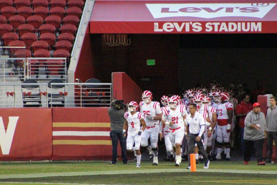 The varsity Monarchs run out from the locker room.
