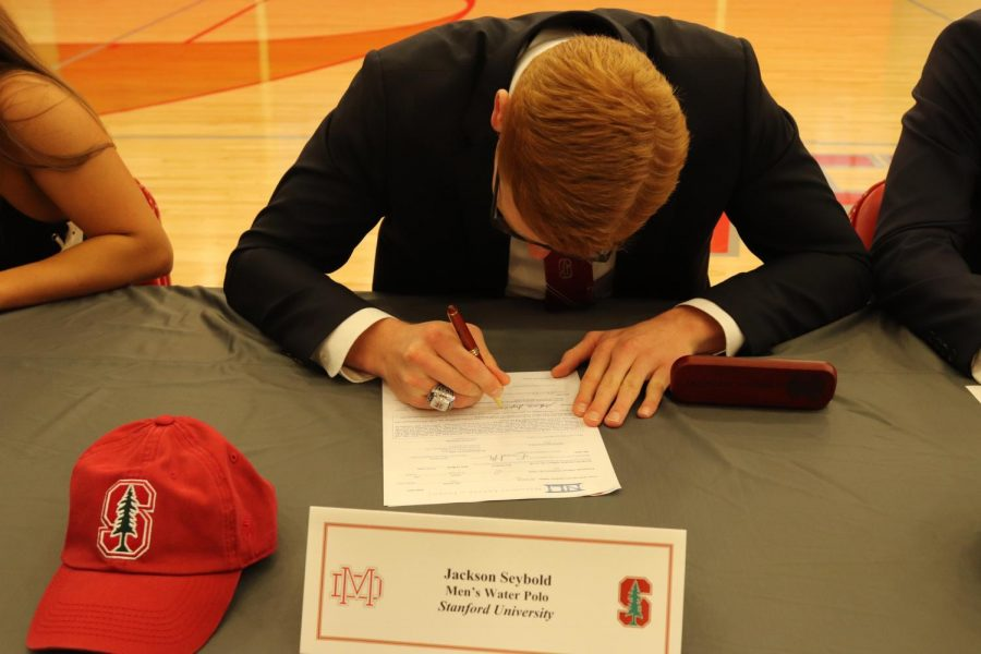 Water polo's Jackson (Jack) Seybold commemorates this event by signing paperwork from Stanford University while wearing his CIF championship ring.