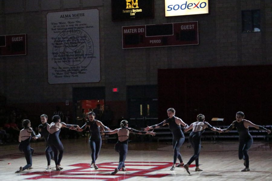 The dance team grasps each other's hands as they perform their fall routine to the song