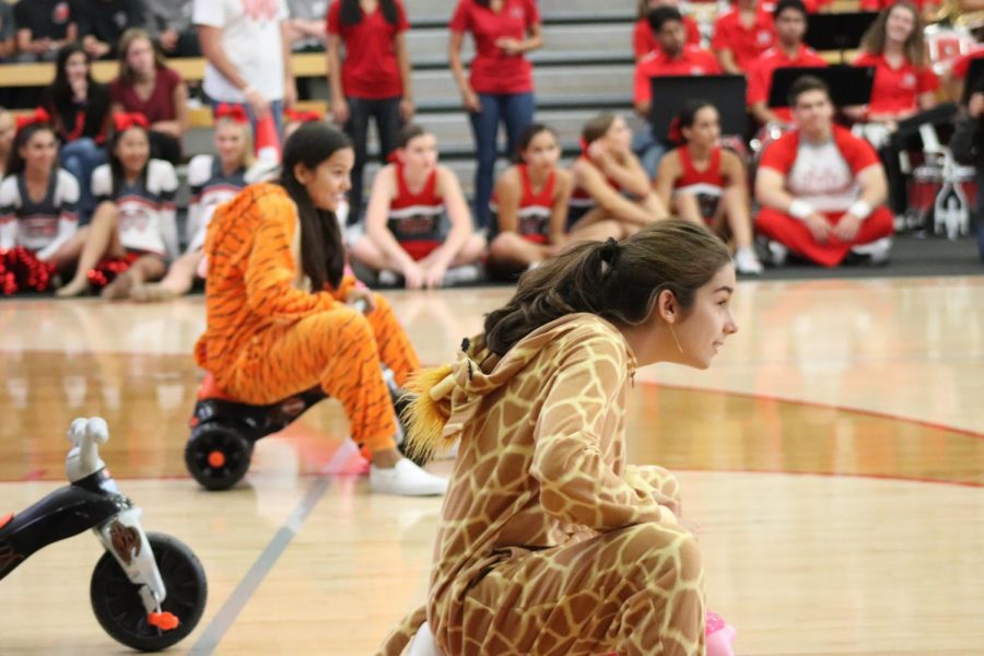CIRCUS ON WHEELS: Senior Sofia Galindo and junior Anne-marie Verkuylen roll around in tiny tricycles as they participate in the relay event that featured various fall sport athletes.