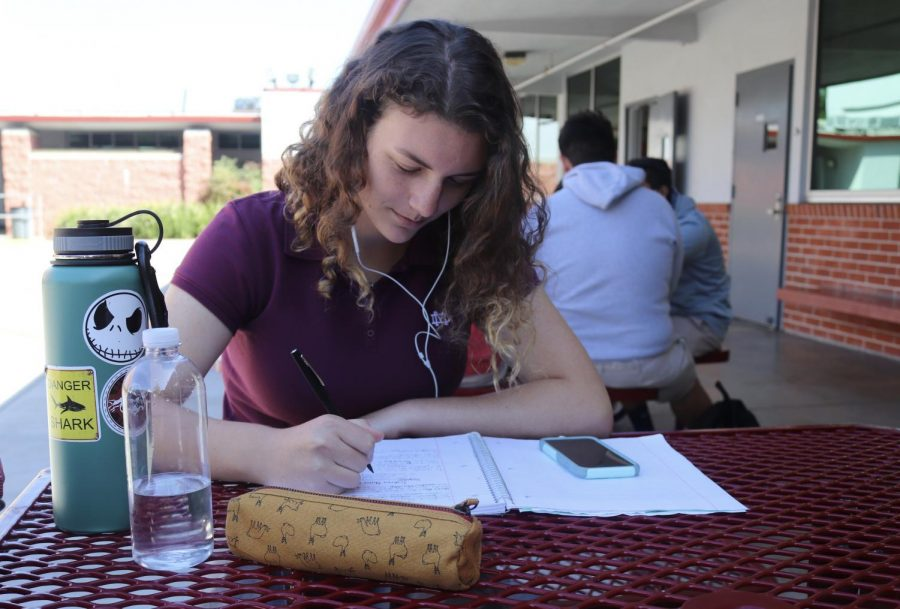 """Junior Madison Warnock enjoys music while completing a homework assignment outside of the LeVecke Center. """"My favorite song while doing homework would have to be 'Ophelia' by the Lumineers,"""" said Warnock, who is a composer and is involved in the school's music program."""