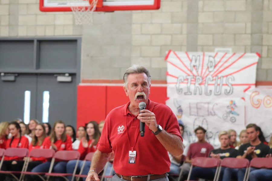 ROCK & ROLL: Coach Bruce Rollinson makes remarks about the football season, encouraging students to dress in red, white, and blue in honor of Labor Day for their game against La Mirada game.