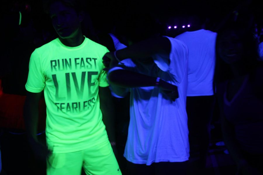 LIVE FEARLESS: Seniors Charles Jensen and Brison Nguyen take advantage of the Welcome Dance's dark light as they become human glowsticks. The annual Welcome Dance took place on Sept. 8 in the Meruelo Athletic Center.