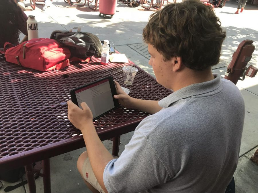 STUDENT STUDIES: Sophomore Russell Barone checks his homework assignments during lower lunch. Many students thinks that Canvas is more user friendly than its predecessor, Blackboard.
