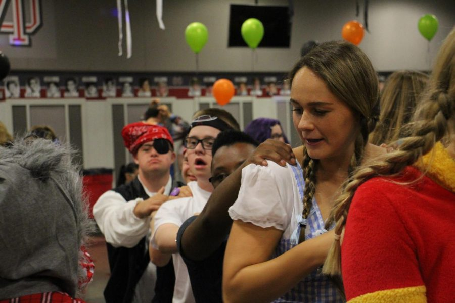 JUMP IN LINE: Senior Hannah Constandse leads a conga line of volunteers and guests around the dance floor. Boo Bash was held on Oct. 6 in the LeVecke center from 6 to 10 p.m. for teens and young adults in the down syndrome community.