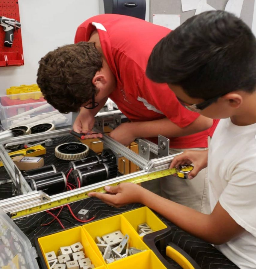 Working in the new robotics labs, senior Ralph Gastelum (left), robotics team captain, adjusts a robot, as his team member aids in measurements. Gastelum has been a part of the team ever since freshmen year. He said being on the team has provided him with lots of life long lessons.