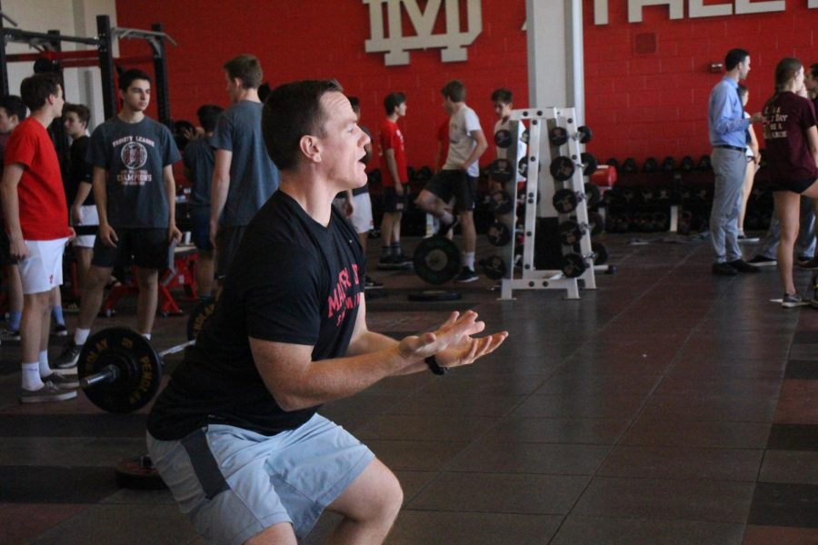 LEADING THE WAY: Assistant strength and conditioning coach Bubba Reynolds instructs the girls volleyball team on the proper form for their workout. Reynolds helps coach many teams during the many weight lifting blocks.