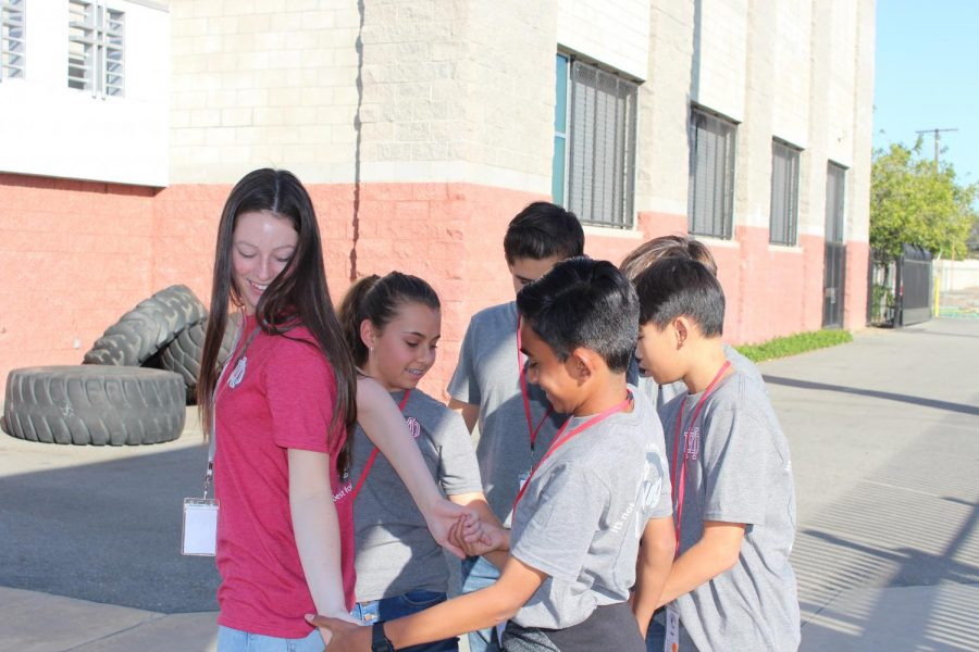 "TANGLED TEAMWORK: ASB leader and junior Jill Neustadt works with her middle-school students to untangle themselves in the ""Human Knot"" challenge at the end of the Learning to Lead event on Nov. 11. The station was just one of many in the leadership challenge put towards the end of the day. Groups had to work together at the various stations in order to finish first and win a prize."