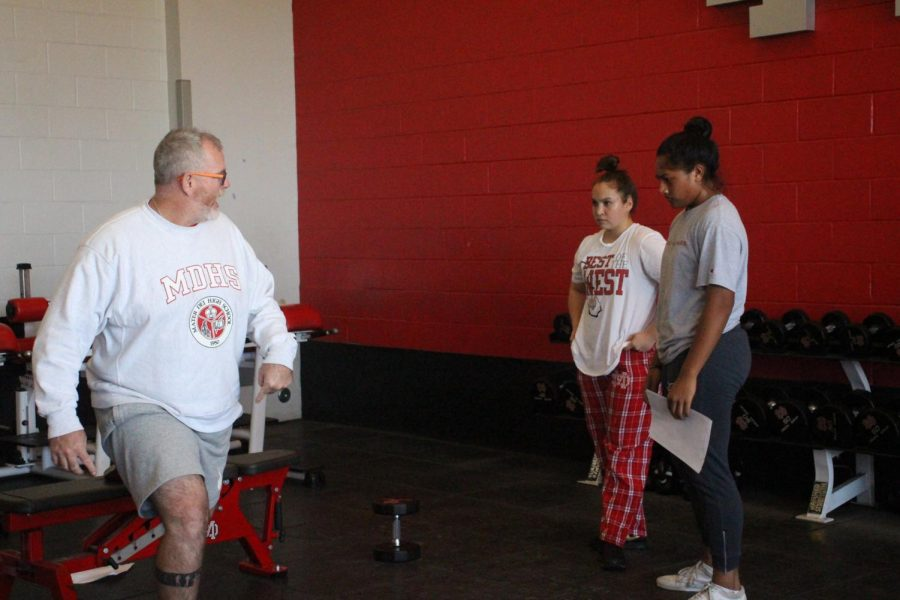 STEPPING UP THE GAME: Head strength and conditioning coach Chris Holder instructs volleyball players Mia Tuaniga and Victoria Mejia on proper weightlifting technique. The team is working extra hard after just winning state.