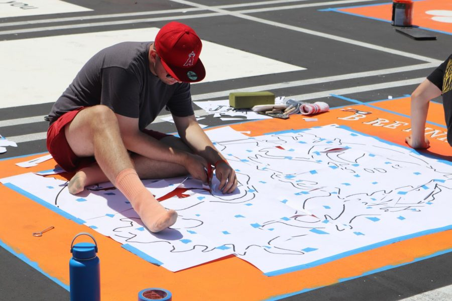 PAINTING THE BIGGER PICTURE: Senior James Brenninkmeijer begins to design his personal parking spot on Aug. 12. The seniors paid $500 for their spots which benefitted as a fundraiser for the construction for the new ASB building.