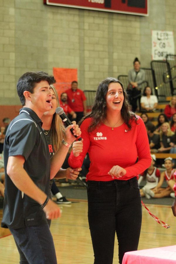 MIC MADNESS: Two students quickly pick up the mic and awkwardly finish a song. In a game, students and teachers raced to finish the lyrics of throwback songs played.