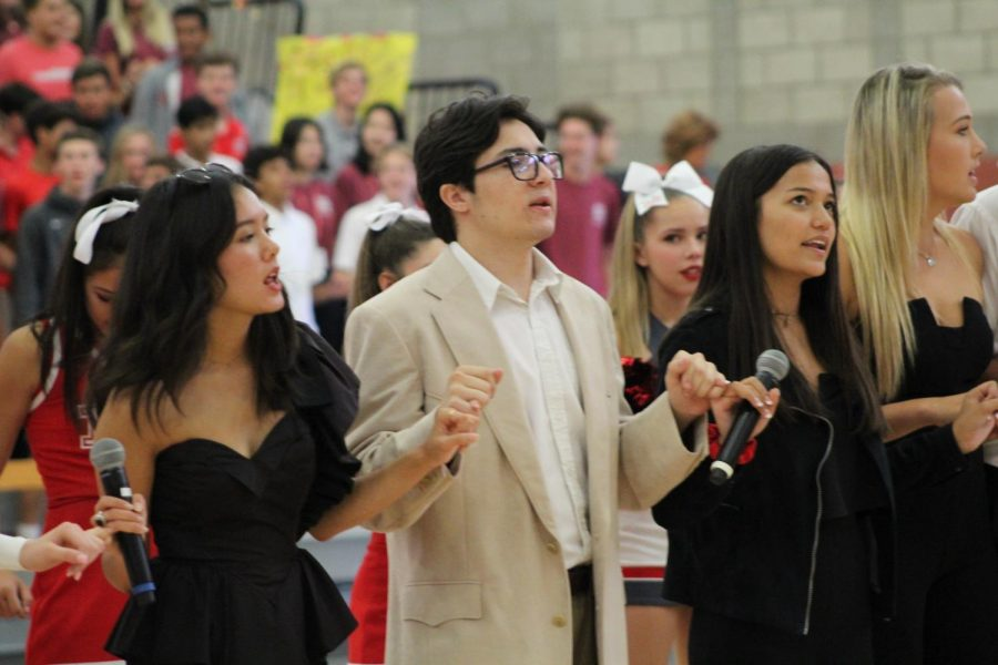 COMING TOGETHER: At the end of the rally, the Rally Commissioners link pinkies together and sing the Alma Mater. As a tradition, the student body united under the school theme song.