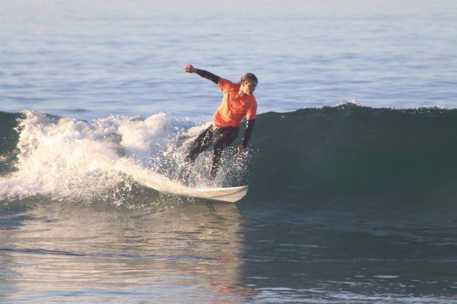 During+the+surf+team%27s+match+against+Corona+del+Mar%2C+freshman+Oliver+Hobin+rides+a+wave+in+front+of+the+judges+at+Huntington+Beach+tower+5+on+Oct.+24.