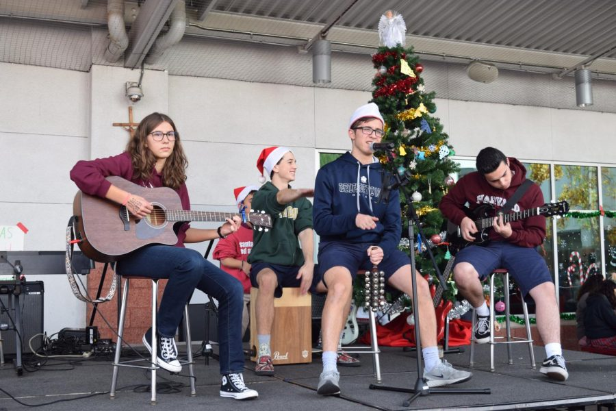 "COMPETING FOR A CAUSE: Junior Maggie Ambrose, senior Joseph Solorio, junior Connor Bogart, and senior Grant L'Heureux, who are all in the block 2 Advanced Guitar class, perform in the guitar Christmas concert on Dec. 11 during upper lunch in the Monarch Pavilion. This concert was a competition between the guitar classes that raised money by selling hot chocolate to buy toys for the annual Christmas Outreach. ""My guitar class is about learning how to play songs by picking chord progressions that have variety and sound good,"" Ambrose said."