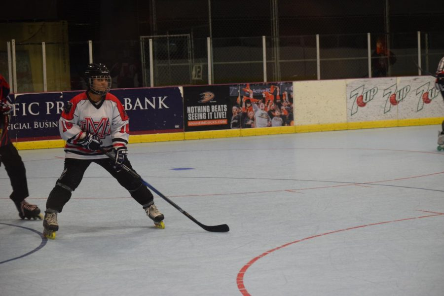 Female player skates up to the puck and accepts the challenge
