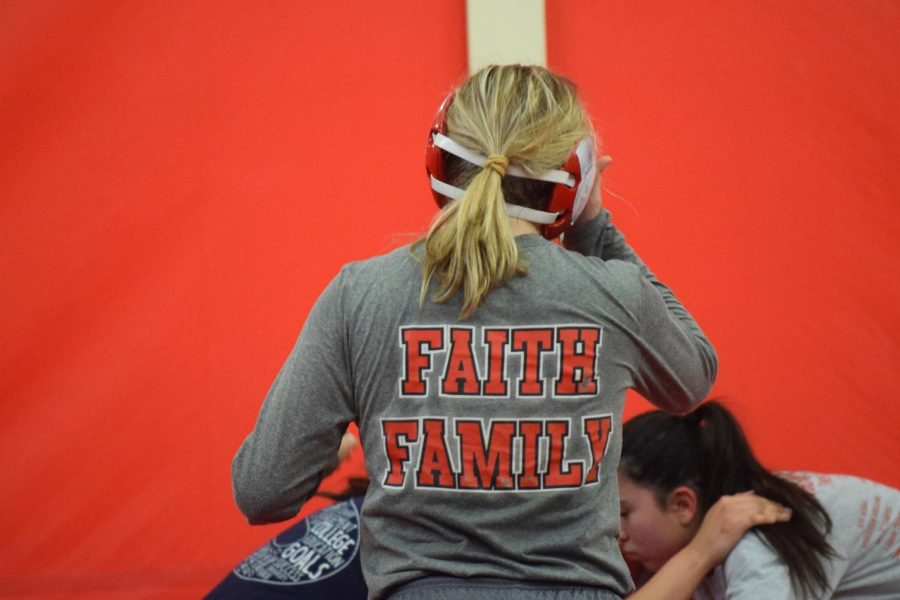"""FAITH, FAMILY, TEAM:  Doran watches her practice opponents as they wrestle each other and waits for her turn to go up against them. The wrestling team motto is """"faith and family"""". """"You go out there as an individual but all together its a team sport because you help each other get better and you motivate each other,"""" Doran said. """"In the end, when I win, I not only do it for myself but for my coaches and for my team."""""""