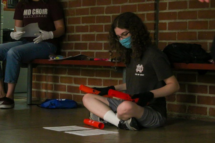 "STAY TUNED: In order to get some practice in, senior Katherine Wieland carefully studies her sheet music. While doing this, Wieland also rehearses by tapping the Boomwhackers against her knees to each note. ""What I like most about working with the boomwhackers is that they are easier to handle than the Handbells,"" Wieland said.""I just need to focus on hitting the boomwhacker correctly to get the right sound."""