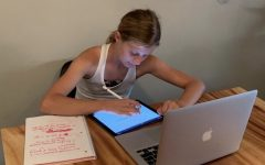 "STUDYING HISTORY WHILE LIVING THROUGH IT: Sophomore Willow Laws works on a history worksheet on her iPad at home on Oct. 13. Laws' history class, taught by Justin Deskovick, is considered an asynchronous class where she is given assignments and assessments to complete on her own on time and is self-paced for students fully online. ""I feel like I've gotten used to [online school] but it is still a little weird,"" Laws said. ""I only have Zoom classes for two of my classes [Religion and Spanish] so I haven't really seen who my teachers are yet. I feel like I can make it work because all of my teachers are always emailing me and reaching out to me."""