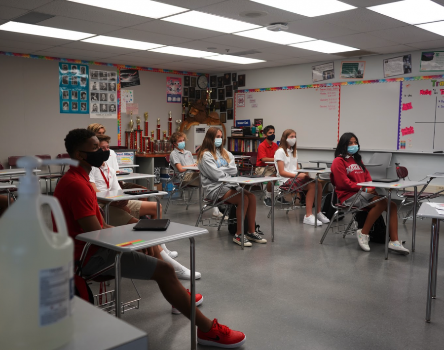 "EYES UP, MASK ON: Students sit at their desks with their masks on and listen to their teacher. During the Hybrid Learning program, students are required to wear masks at all times while on campus, and teachers like Mrs. Kitsinis feel that change the most in their classrooms. ""There"