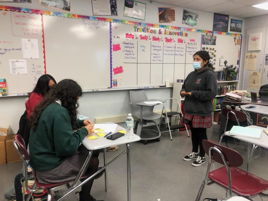 Students prepare for their debate and practice with one another. One student goes up to practice in front of her two other classmates.