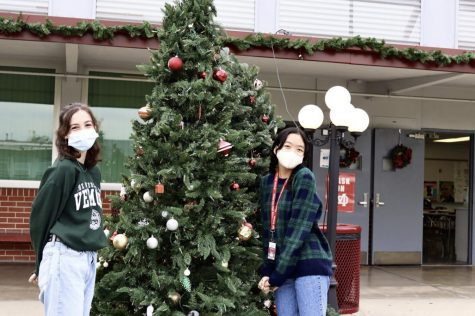 "DECK THE HALLS To celebrate the Christmas spirit, the grotto was dressed up with Christmas trees, garlands, and lampposts in order to spread the contagious holiday spirit. Freshmen Marieka Erhard (left) and Hannah Franco (right) pose in front of one of the Christmas trees. Erhard's favorite Christmas decoration to see is the Christmas lights. ""They just make me feel better,"" Erhard said."
